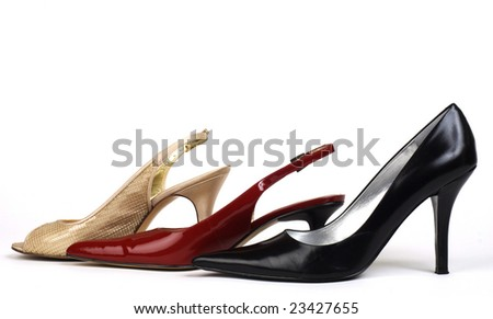 A shot of one gold, one red, and one black women's high-heel dress shoe against white background - stock photo