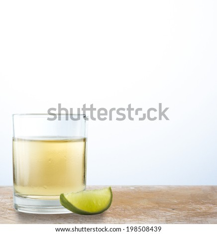 A shot of scotch with lime on wooden table - stock photo