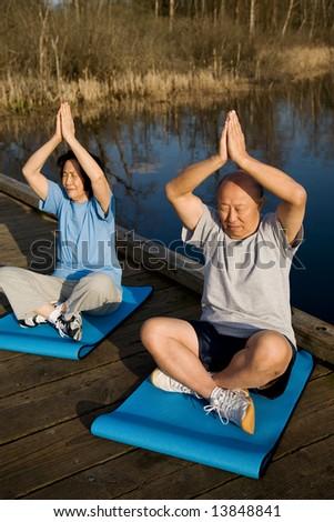 A shot of senior asian couple meditating and practicing yoga - stock photo