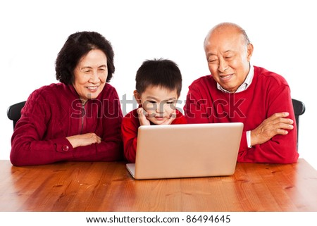 A shot of senior Asian grandparents using computer with their grandson - stock photo