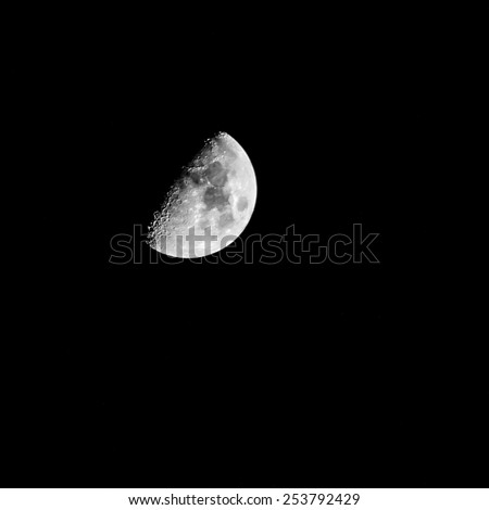 A shot of the moon hanging in the night sky. - stock photo