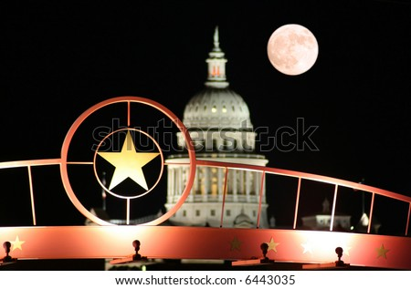 A shot of the star of Texas with the Texas State Capitol Building and the moon in the background. - stock photo