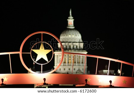 A shot of the star of Texas with the Texas State Capitol Building in the background. - stock photo