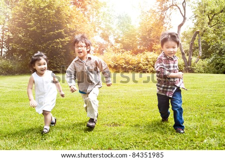 A shot of three Asian kids running in a park (focus in the middle kid) - stock photo