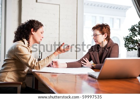 A shot of two businesswomen working in the office