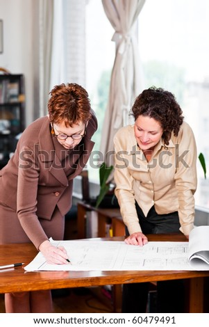 A shot of two businesswomen working in the office - stock photo