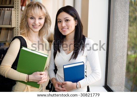 A shot of two college students in a library - stock photo