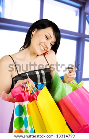 A shot of woman holding shopping bags and calling her credit card bank - stock photo
