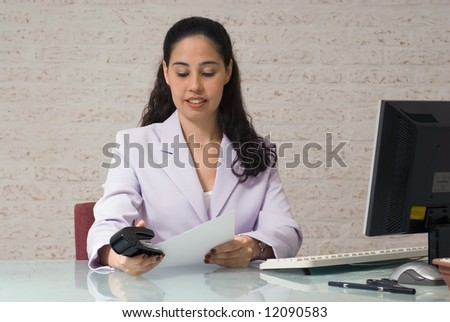 A shot of young businesswoman stapling documents together. - stock photo