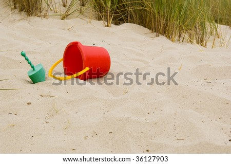 A shovel and a bucket on a sandy beach with grass, includes copy space - stock photo