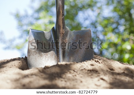 A shovel is stuck in a pile of dirt with bokeh in the background. - stock photo