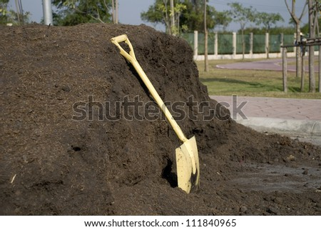 A shovel leaning against a mound of dirt.
