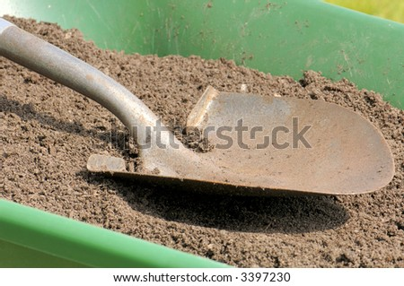 A shovel rests on sandy topsoil in a wheelbarrow. Focus = dirt near footstep. 12MP camera. - stock photo