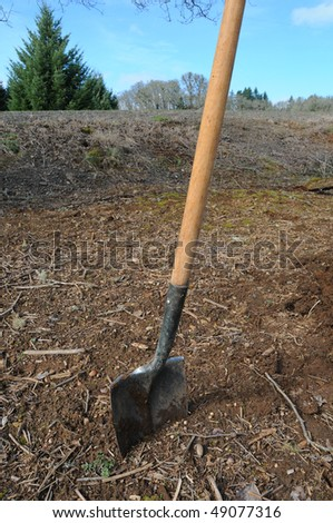 A shovel stuck in dirt. It appears to have been used before. Yard work.