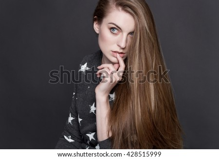 A shy young blonde girl in a gray sweater. She sensually touches her lips with his finger. She's smart and curious. Her luxurious shiny hair, clear skin and a delicate blush. - stock photo