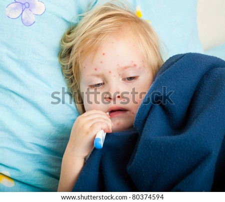 a sick cute girl is measuring the temperature - stock photo