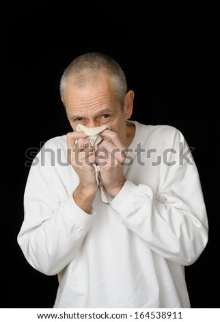A sick man with cold holding an handkerchief in hands and blowing his nose - stock photo