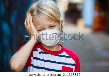 A sick upset boy with a headache is wearing a protective face mask. - stock photo