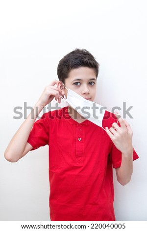 A sick young boy putting on a face mask to stop spread of germs. - stock photo