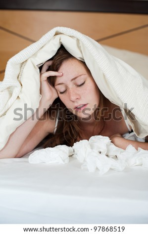 A sick young lady in bed, lying with her head under the blankets and a pile of tissues in front of her. - stock photo