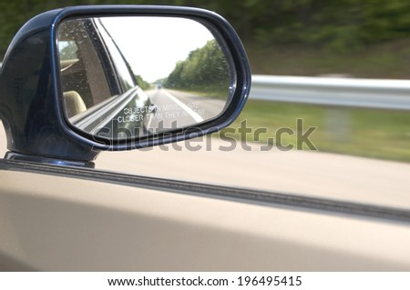 A side mirror on a car reflecting the road. - stock photo