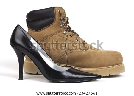 A side shot of one black women's high-heel dress shoe sitting beside a brown work-boot, against white background - stock photo