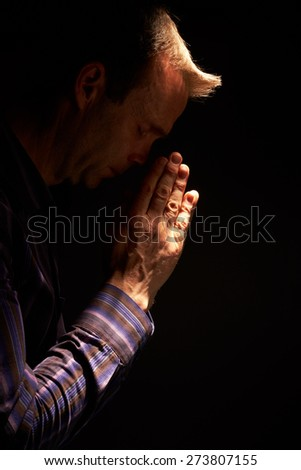 A side view of a man praying with a ray of sunlight shining down on him. Instagram styling applied. Small amount of added grain. - stock photo