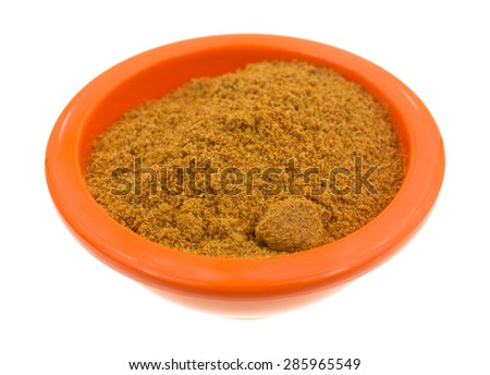 A side view of a portion of grainy cajun seasoning in a small orange bowl. - stock photo