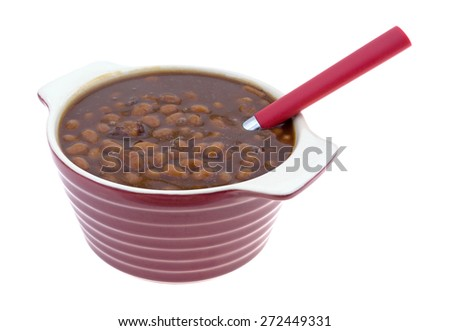 A side view of a serving of canned county style beans in a maroon and white striped serving dish. - stock photo