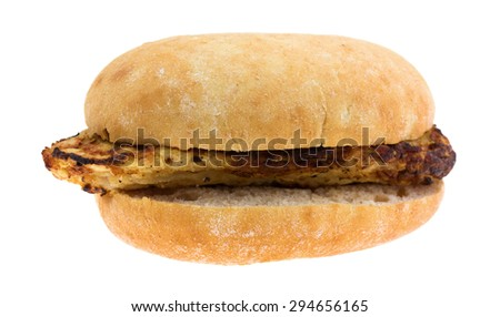 A side view of an open grilled chicken sandwich on a white background. - stock photo