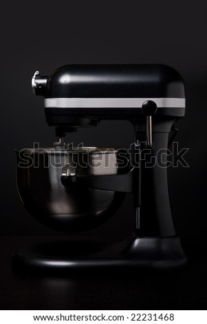 A side view of professional black and silver mixer and beater against a black background.