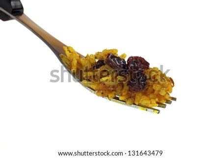 A side view of spicy rice and raisins on a fork. - stock photo