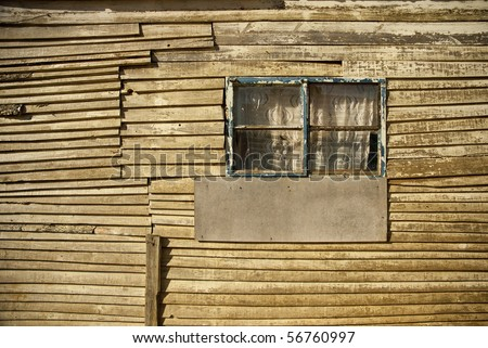 A side window of a wooden shack in a township in South Africa - stock photo