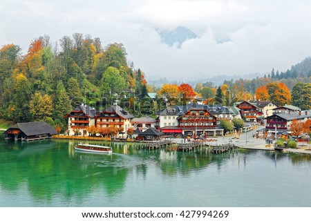 A sightseeing boat cruising on Konigssee ( King's Lake ) surrounded by colorful autumn trees and boathouses on a foggy misty morning~ Beautiful scenery of Bavarian countryside in Berchtesgaden Germany - stock photo