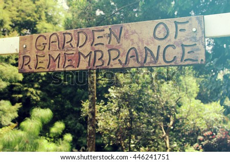 A sign above the entrance to a garden of remembrance where the dead are laid to rest. Added vintage filter effect.