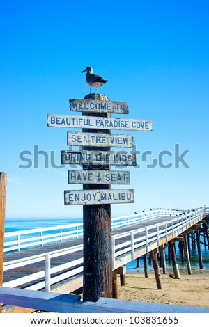A sign and a seagull welcome visitors to the pier at Malibu Beach in California. - stock photo