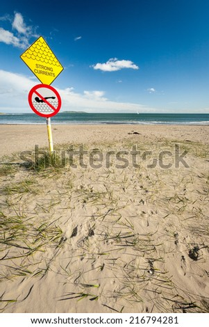 A sign at a sandy beach near Malahide, Ireland, warning people of the strong currents expected in the nearby waters. - stock photo