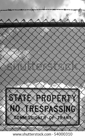 A sign behind a chain linked fence with barbed wire that reads STATE PROPERTY NO TRESPASSING outside an airport - black and white. - stock photo