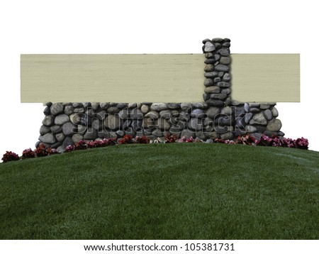 A sign built with river rocks and wood sits atop a green hill. - stock photo