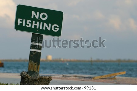 A sign declares no fishing from this spot. - stock photo