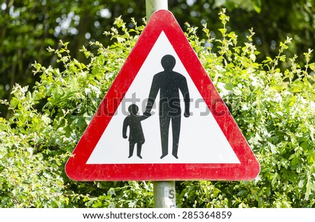 A sign for crossing the road safely UK. - stock photo