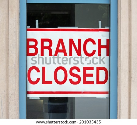 A sign in a store window reading Branch Closed - stock photo