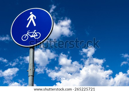 A sign indicates the presence of a pedestrian and bicycle trail.