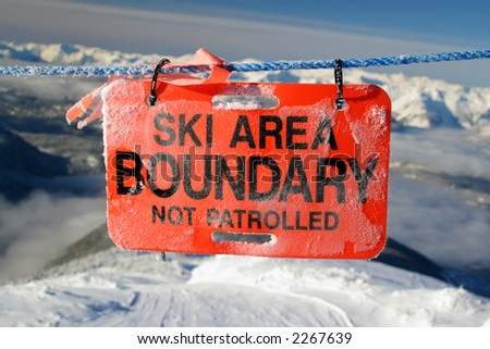 A sign marks the boundary of a ski area. - stock photo