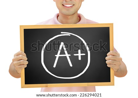 A+ sign on blackboard held by smiling man - stock photo