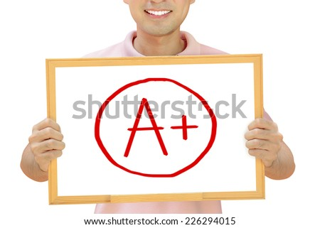 A+ sign on whiteboard held by smiling man - stock photo