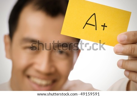 A+ sign on yellow card holding by Asian businessman. - stock photo