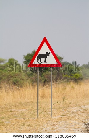 A sign post with a picture of an African wild dog on it