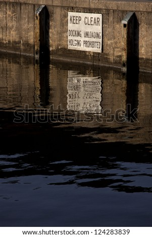A sign posted above the water line at a city dock that warns boaters to Keep Clear - Docking, Unloading, Holding Prohibited. - stock photo