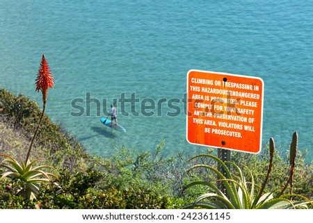 A sign posted on the side of a cliff warning hikers to keep a safe distance from the edge. - stock photo